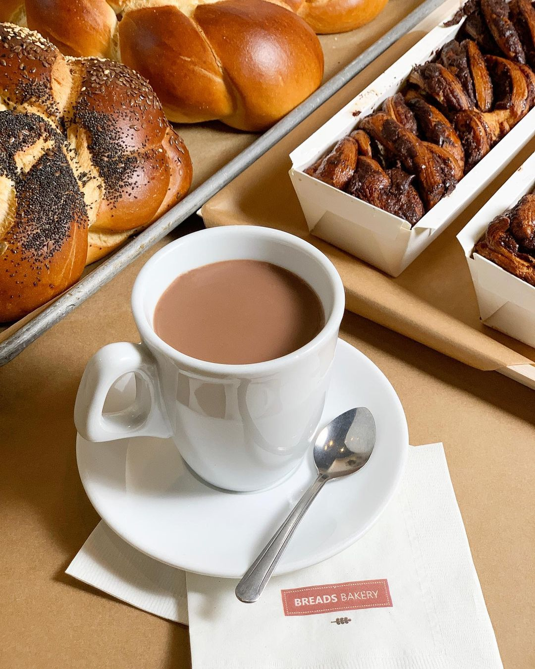 a cup of coffee with a Breads Bakery branded napkin sits in front of a tray of fresh rolls and a tray of chocolate babka