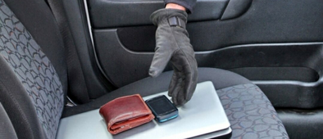 A stock image of a gloved hand reaching into a car to steal a wallet and cell phone.