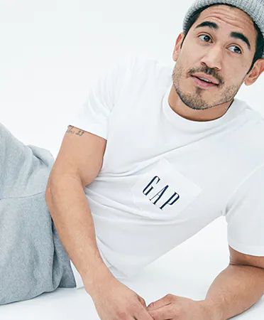 a man in a GAP tee shirt poses on the floor with jeans and a grey beanie