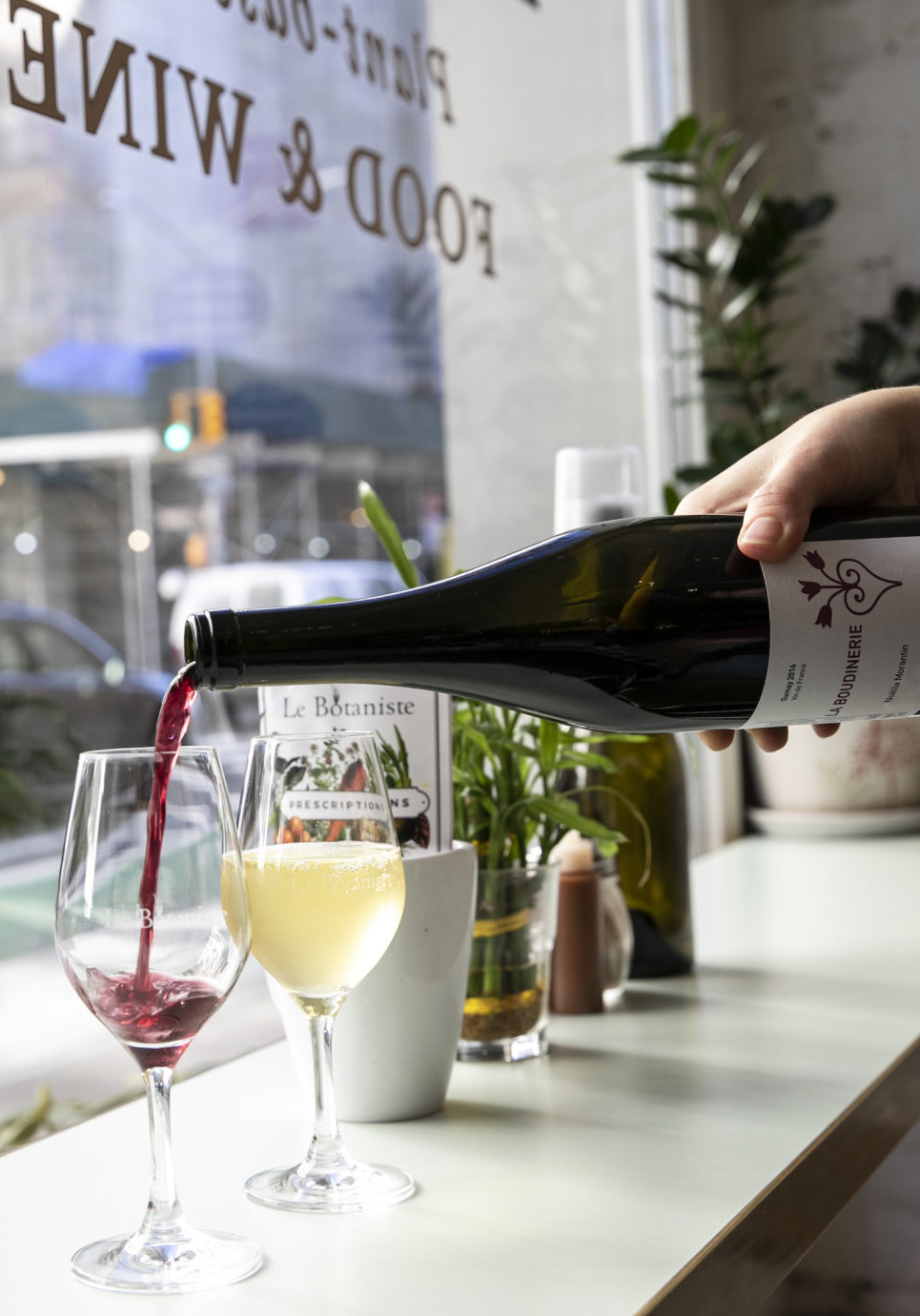 a hand pours a glass of red wine next to a glass of white wine in the window of Le Botaniste