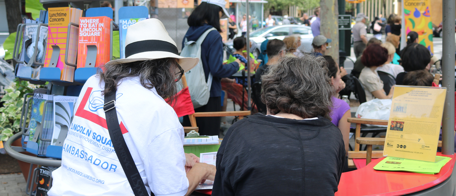 An infomation ambassador gives directions to a visitor at an information cart in Richard Tucker Park
