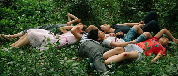 children laying together in the grass from the movie Suburban Birds