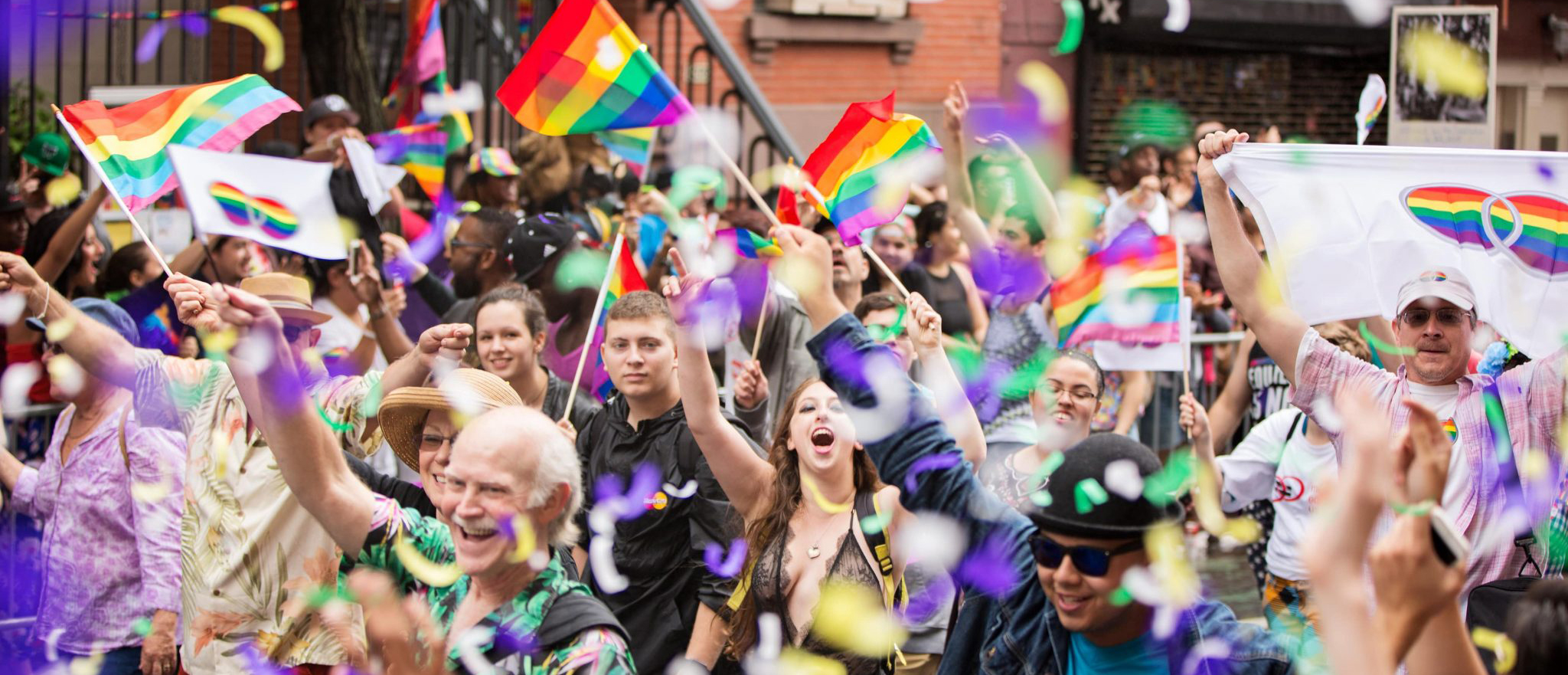 Crowd celebrates Pride in NYC with rainbow flags and confetti