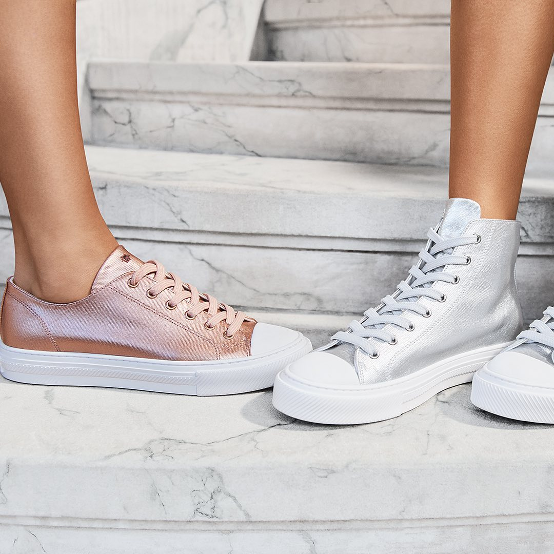 metallic sneakers in pink and silver standing on marble steps