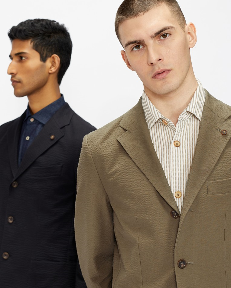 two men pose together in casual spring suits, one is tan and the other is navy