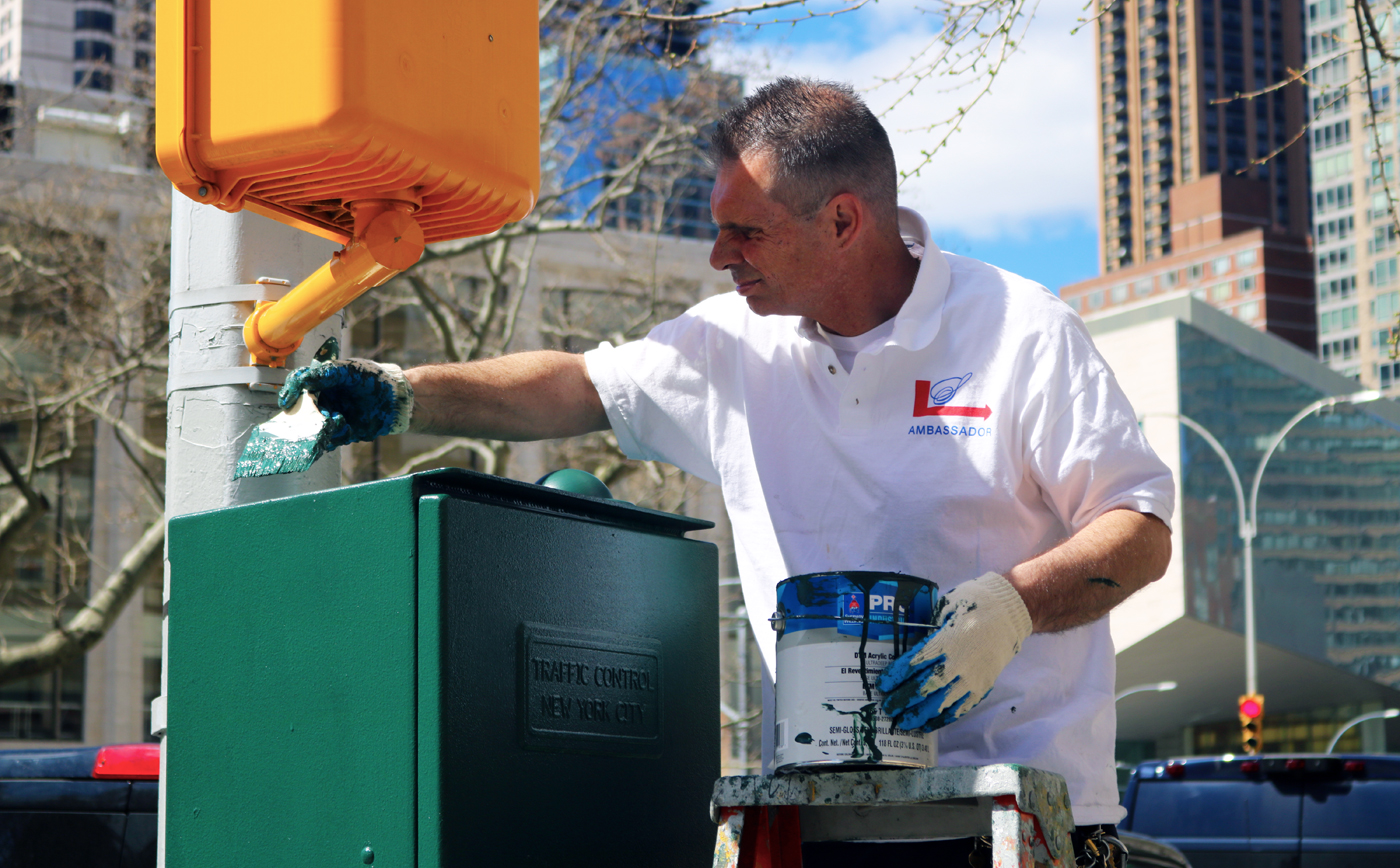 Clean Team Supervisor Tony stands on a ladder to paint a local traffic box