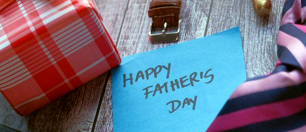 a card envelop sits next to a present and a tie and watch and reads happy father_s day