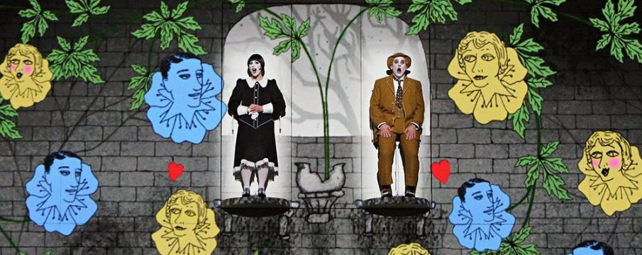 two actors on stage with a CGI background of vines, flowers, and animated faces