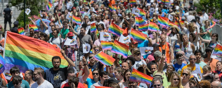 A large crowd of people march for Pride with rainbow flags