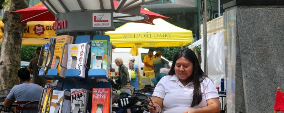 An Information Ambassador  takes notes at an Information Cart in Richard Tucker Park