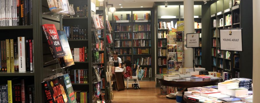 Inside of Shakespeare and Co with book filled shelves
