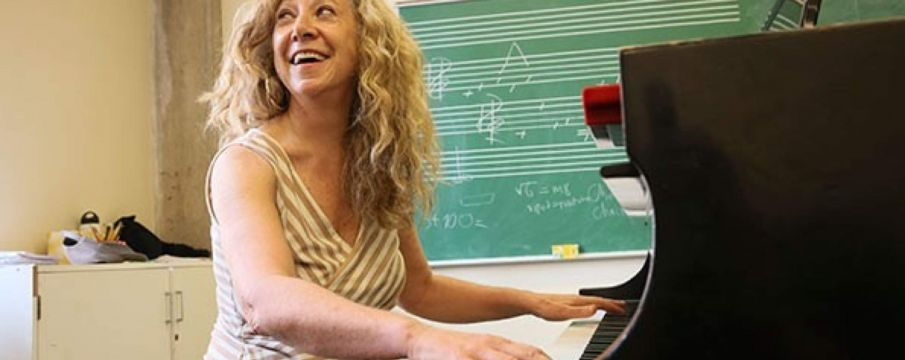woman smiles while playing piano in a classroom