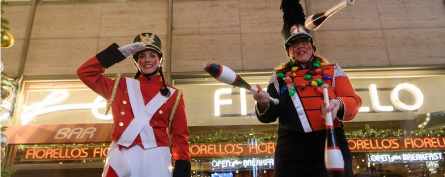 two stilt walkers dressed as soldiers pose for a photo on the street during Winter's Eve