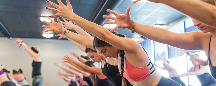 a yoga class stretches forward together in the studio