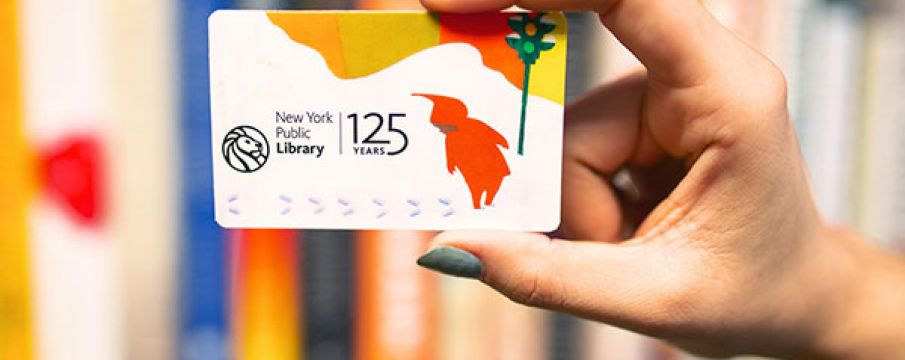a hand with blue painted nails holds up a special edition library card for the 125th anniversary of the new york public library