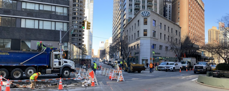 looking down West 62nd St towards Columbus Ave from Broadway with construction trucks and cones on the street