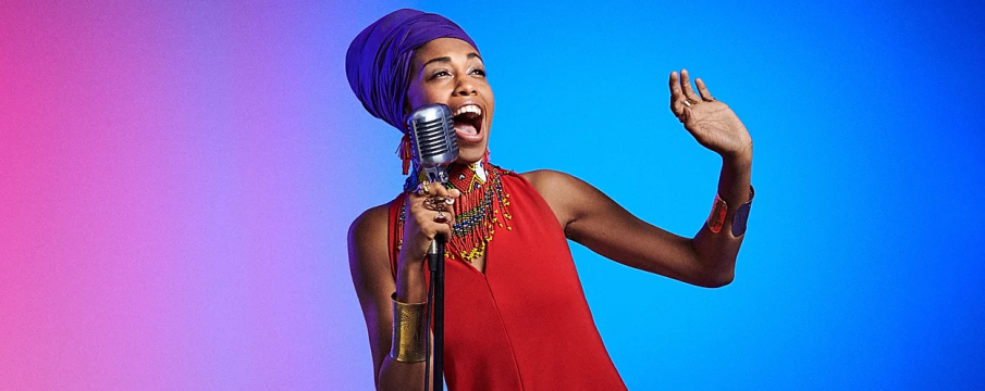 Jazzmeia Horn sings into a mic with a blue and purple background