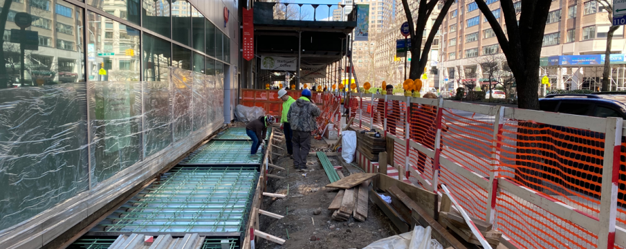 construction workers doing repair work on the sidewalk in front of the AAA building on Broadway