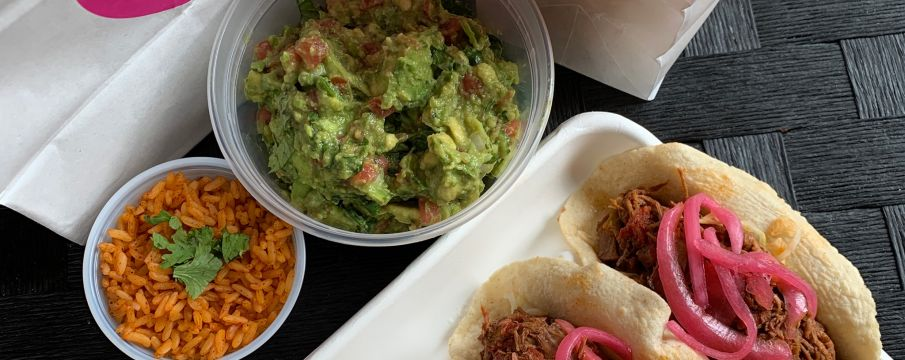 a spread of takeout tacos from rosa mexicano with quacamole and salsa sides