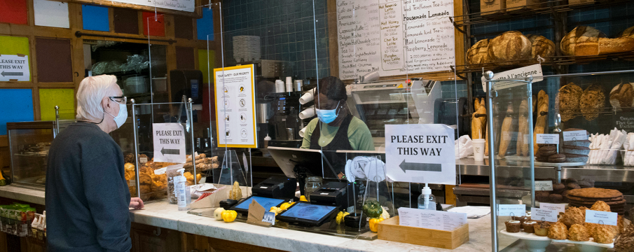 a person in a fleece and a white masks orders from the cashier at Le Pain Quotidien