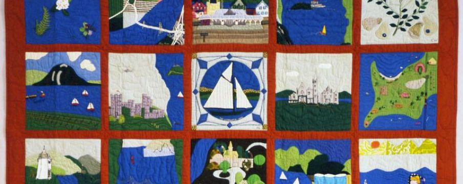 a quilt with mostly blue, greeb, and red fabric, with each square depicting scenes from the Hudson River including boats, landscape, and buildings