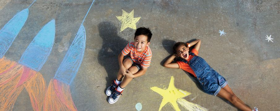 two kids laying on the pavement with chalk drawings around them
