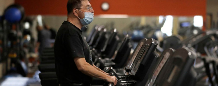 man wearing a mask on a treadmill in a gym