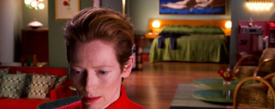 tilda swinton close up to the camera with a living room setting in the background