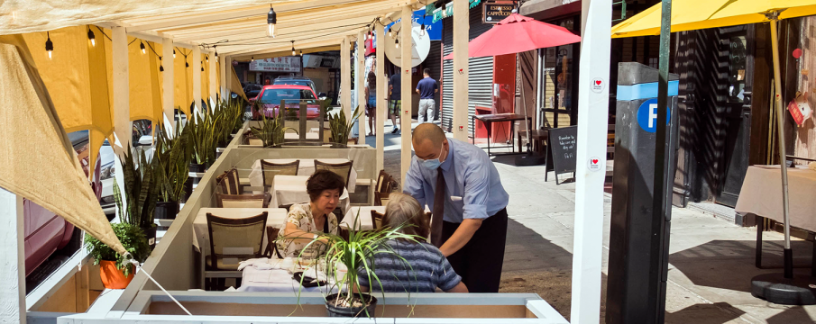 a waiter serving diners outside