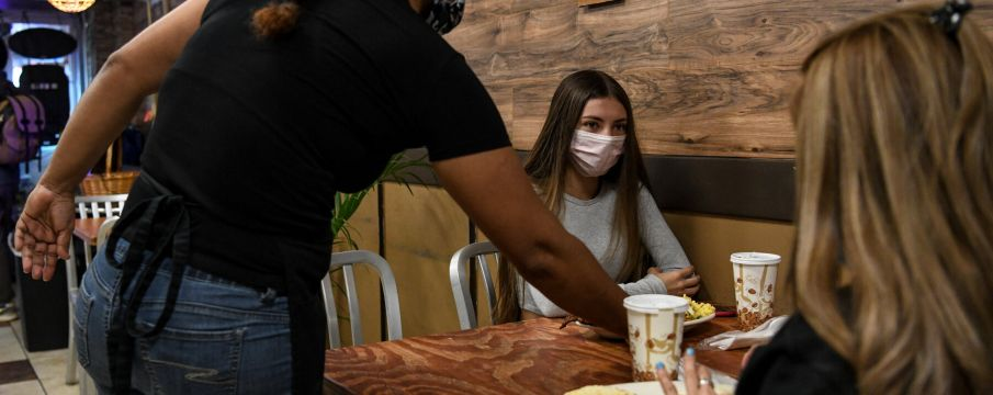a cafe server puts down a plate of food in front of a customer seated inside wearing a mask