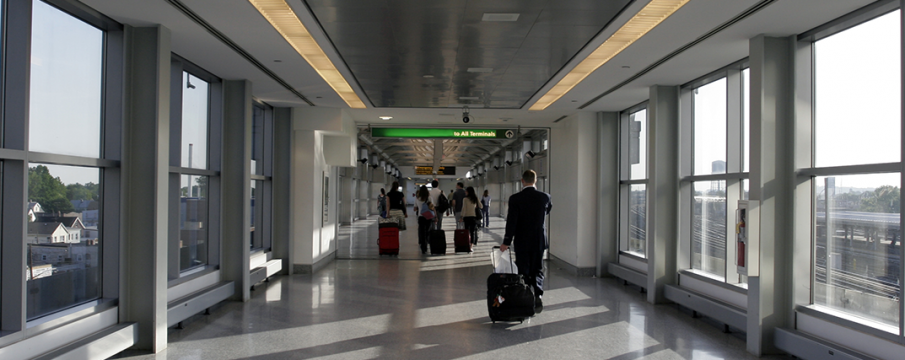 people walking down the pedestrian overpass with luggage at JFK Airport