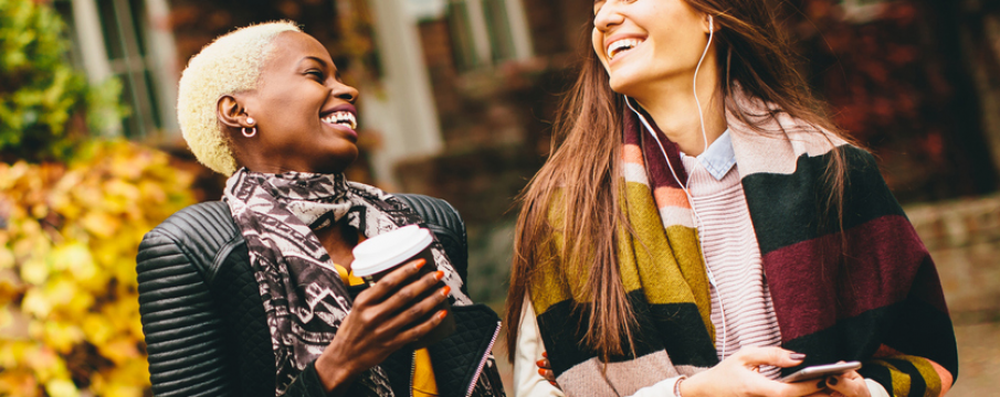 two women laugh and walk with a cup of coffee in stylish fall outfits