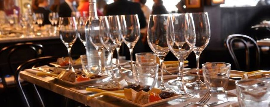 wine glasses lined up on a wooden table with small plates of food