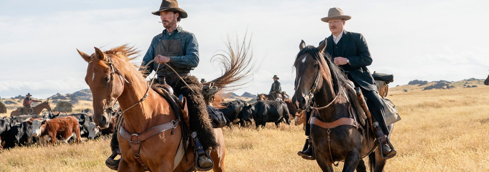 still shot from The Power of the Dog with two men on horseback in a field