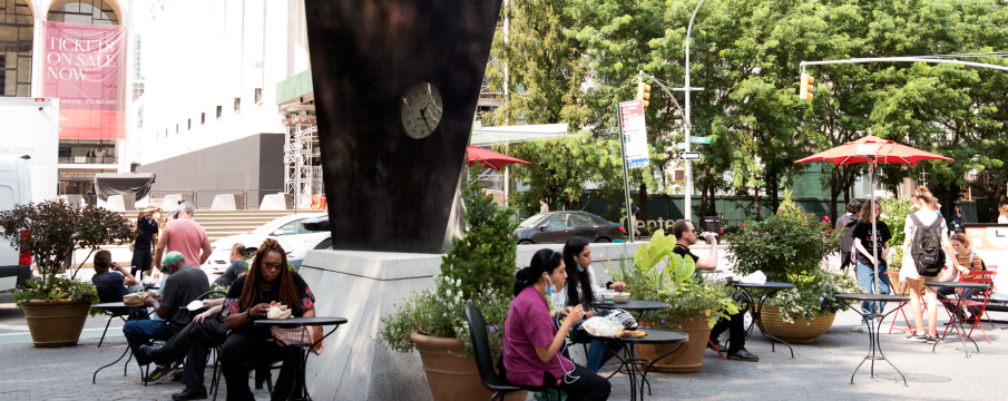 people sit at the tables and chairs provided by the LSBID around the movado clock in dante park