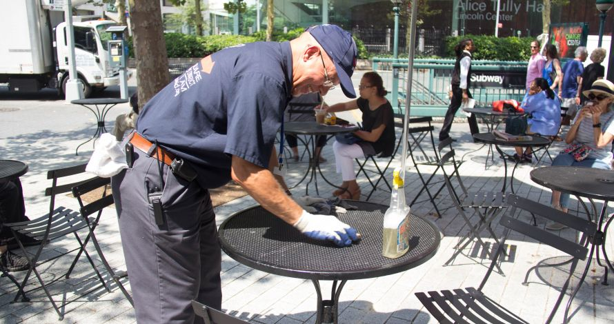 Clean Team Member wipes down an LSBID mesh table in Richard Tucker Park
