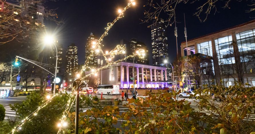 a figure from the BID's holiday lighting installation Tumbling Brights with Lincoln Center in the background